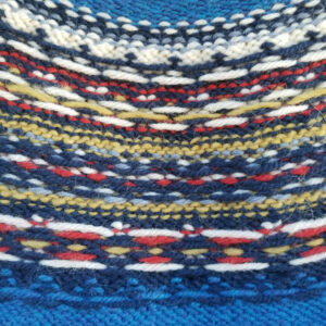 Inside of a yoked fair isle sweater showing yarn floats in primary colors