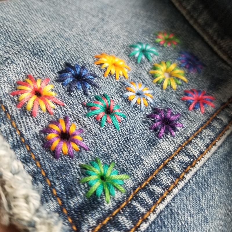 Brightly colored embroidered starbursts mend holes on a denim vest