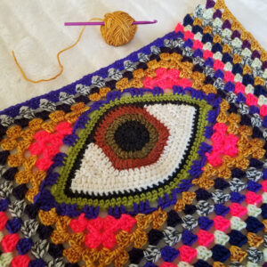 A crochet eye motif surrounded by granny square crochet in a number of psychedelic colors