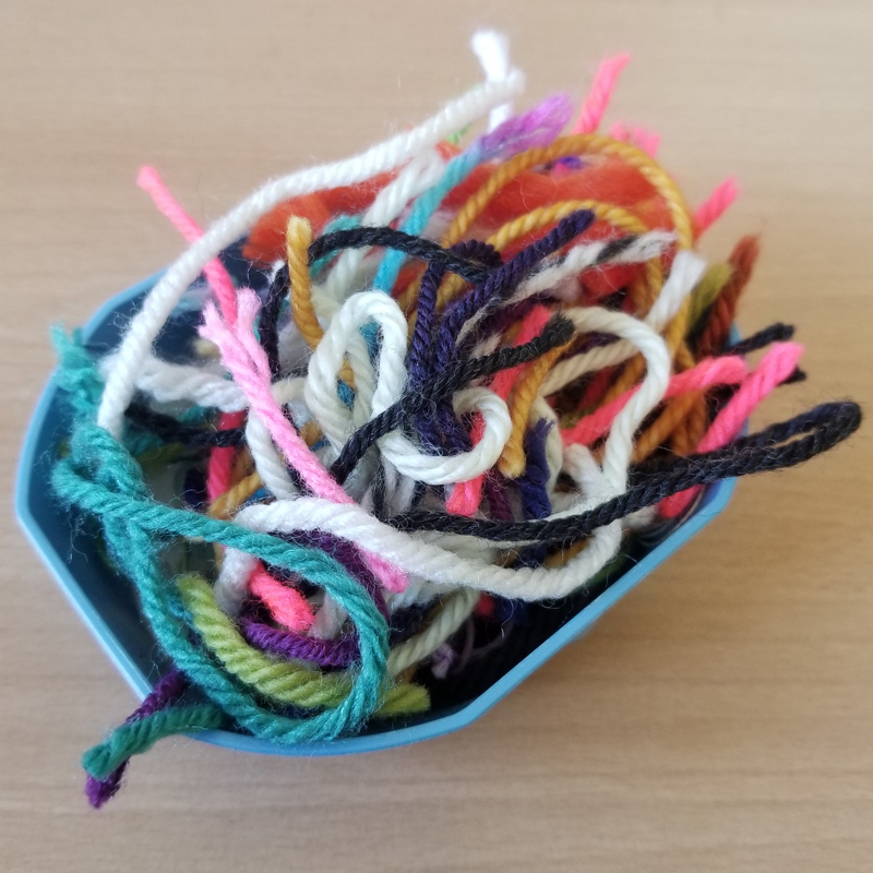 Multicolored scraps of yarn in a small blue octagonal plastic dish.