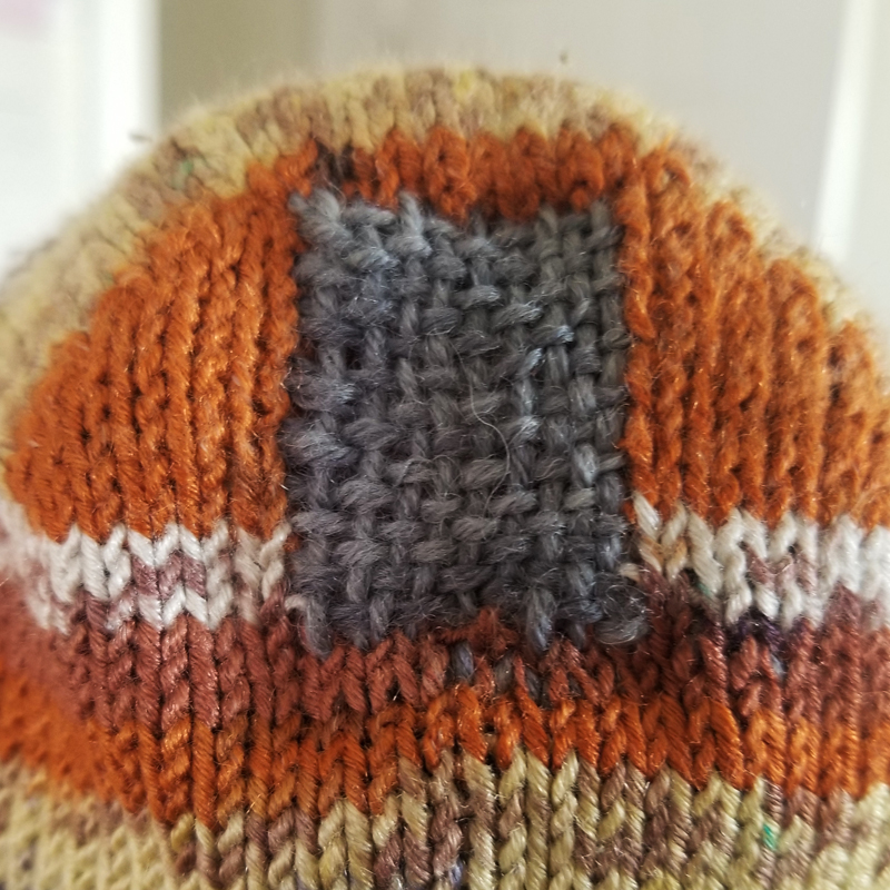 Detail shot of a grey woven patch visibly mending the heel of hand knit brown toned striped socks