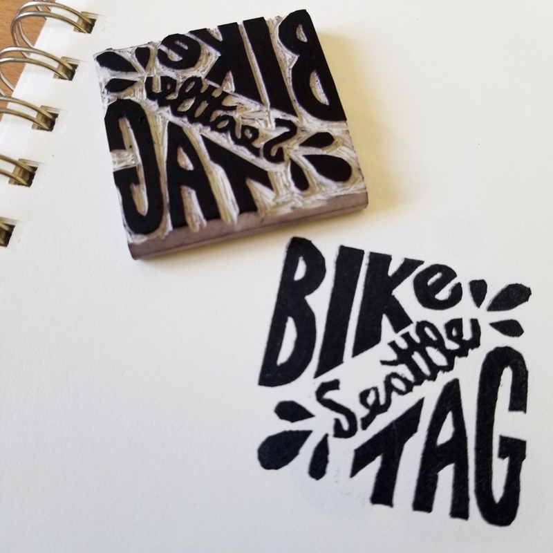 """Small square softcut linoleum stamp next to a print in black ink reading """"Bike Tag"""" with """"Seattle"""" written diagonally across."""