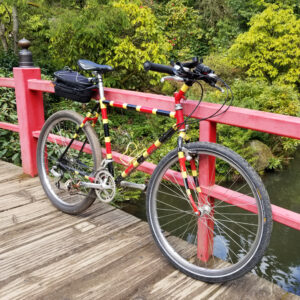 An 80's mountain bike turned commuter bike painted like a coral snake rests against the rail of a Japanese-style bridge.