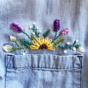 Embroidered sunflower, lavender, and white buds on a chambray shirt just above the pocket
