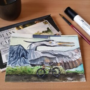 Watercolor postcard featuring a multi-colored commuter bike in front of a blue heron mural.