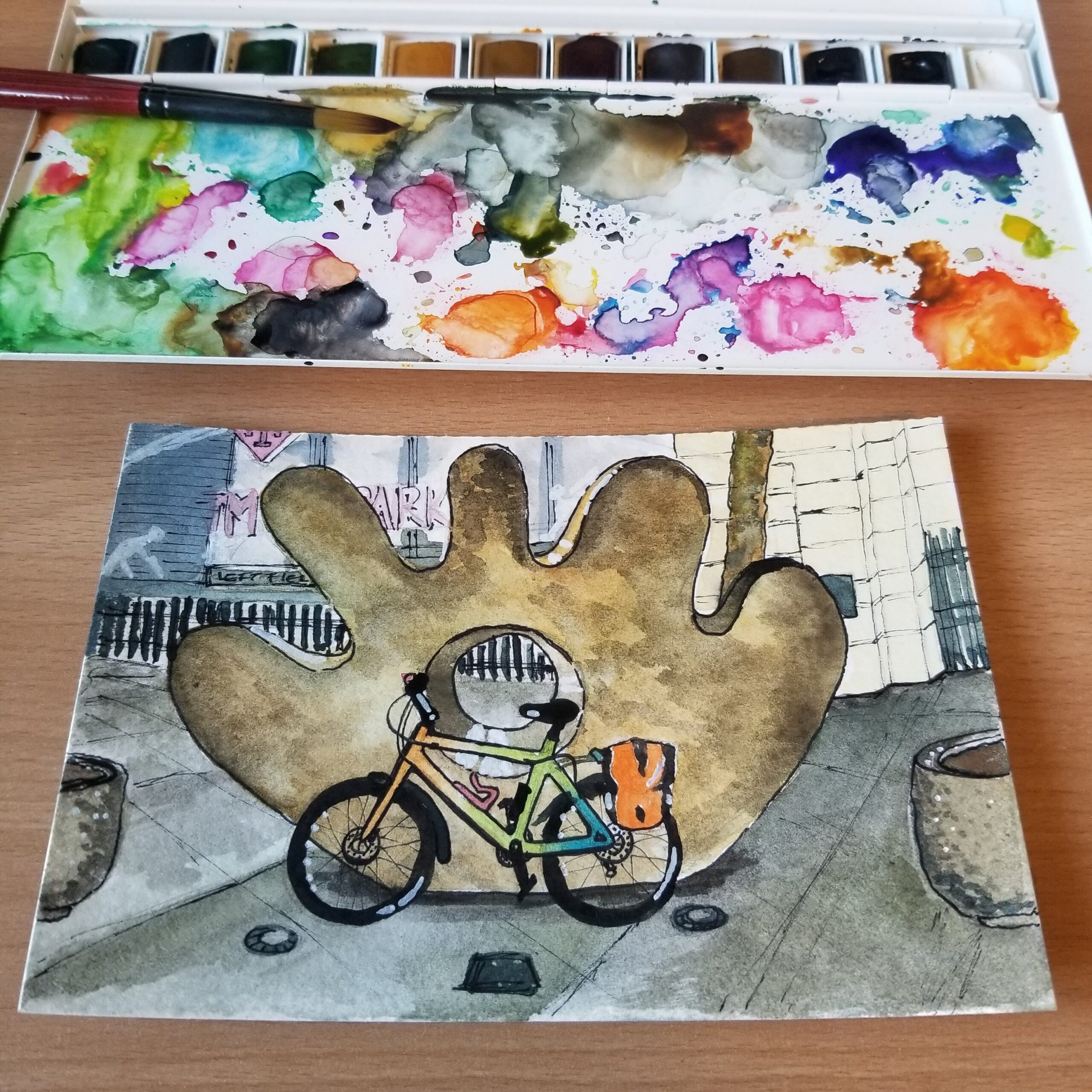 """Watercolor postcard featuring a multi-colored commuter bike in front of Gerard Tsutakawa's sculpture, """"The Mitt"""", at T-Mobile Park."""