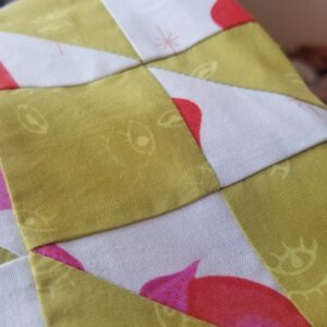 Closeup picture of a fabric bag quilted in yellow ochre and white with pink fabrics in the Amish Star pattern